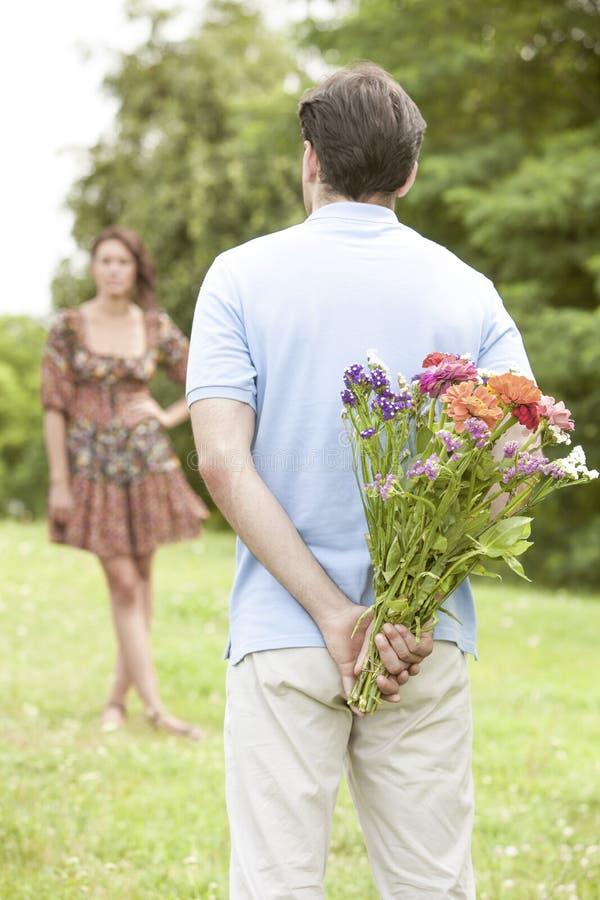 Οπισθοσκόπος να εκπλήξει ανδρών γυναίκα με τα λουλούδια στο πάρκο στοκ φωτογραφίες