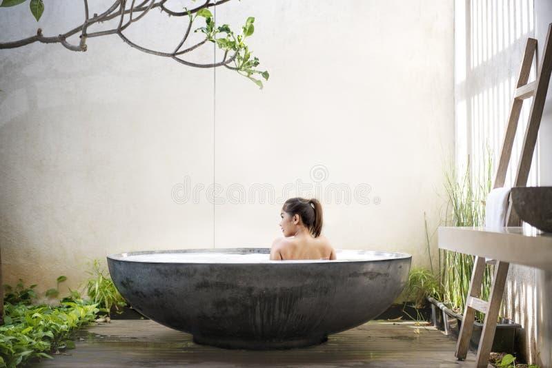 Οπισθοσκόπος της ασιατικής χαλάρωσης γυναικών στην μπανιέρα στοκ εικόνα
