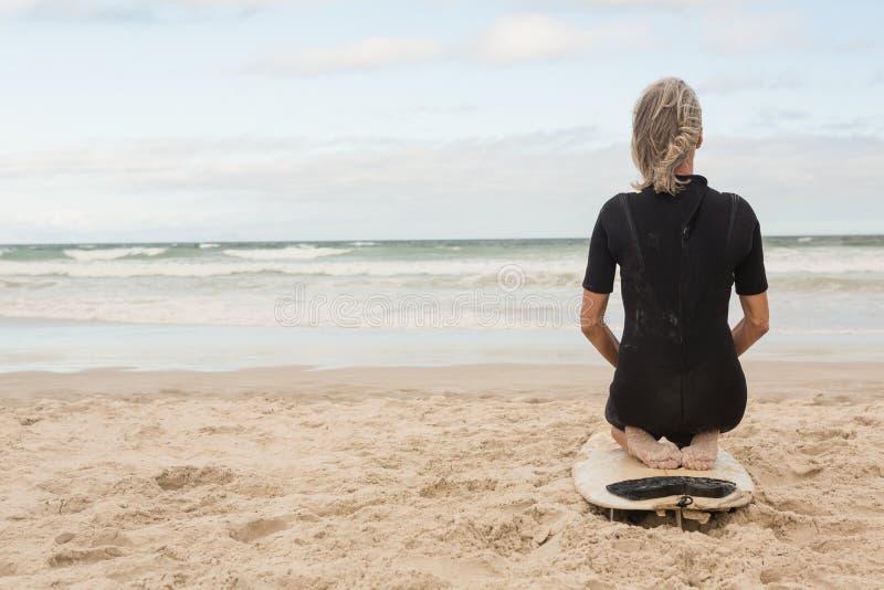 Οπισθοσκόπος της ικεσίας γυναικών στην ιστιοσανίδα ενάντια στο νεφελώδη ουρανό στοκ εικόνες με δικαίωμα ελεύθερης χρήσης