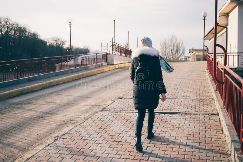 Οπισθοσκόπος της νέας γυναίκας στο κάτω σακάκι που περπατά στην οδό στοκ φωτογραφία με δικαίωμα ελεύθερης χρήσης