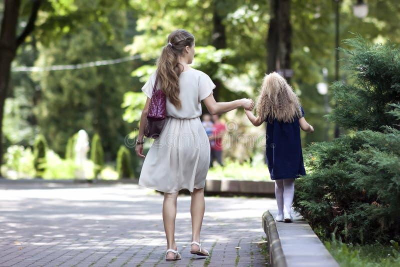 Οπισθοσκόπος της νέας μητέρας που περπατά με την κόρη μικρών κοριτσιών μέσα στοκ φωτογραφία