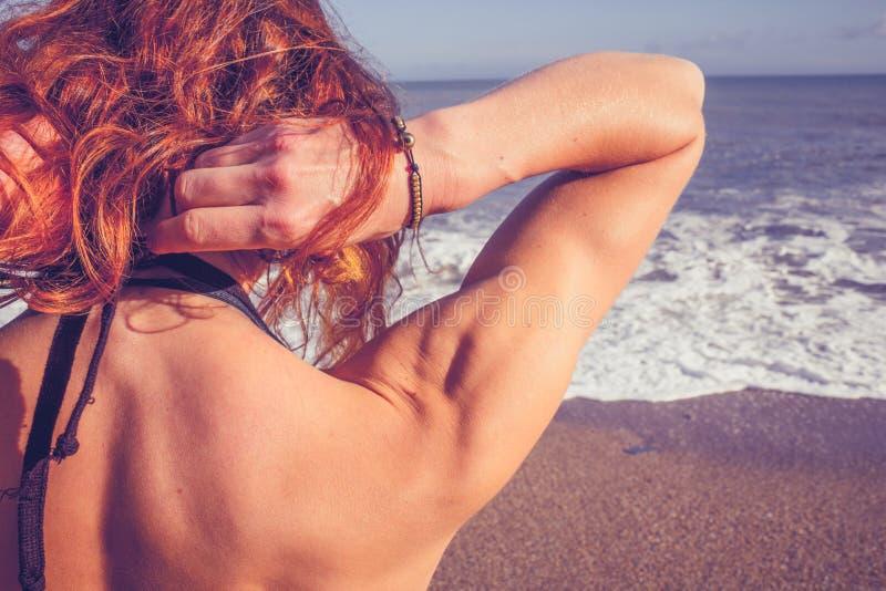 Οπισθοσκόπος της νέας στάσης γυναικών στην παραλία που φαίνεται εν πλω στοκ εικόνες