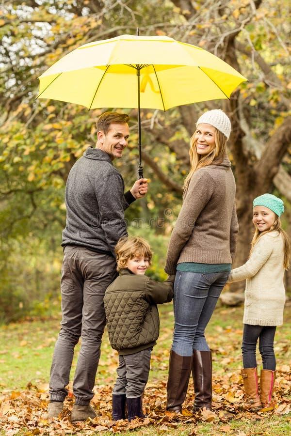 Οπισθοσκόπος της νέας χαμογελώντας οικογένειας κάτω από την ομπρέλα στοκ φωτογραφία με δικαίωμα ελεύθερης χρήσης