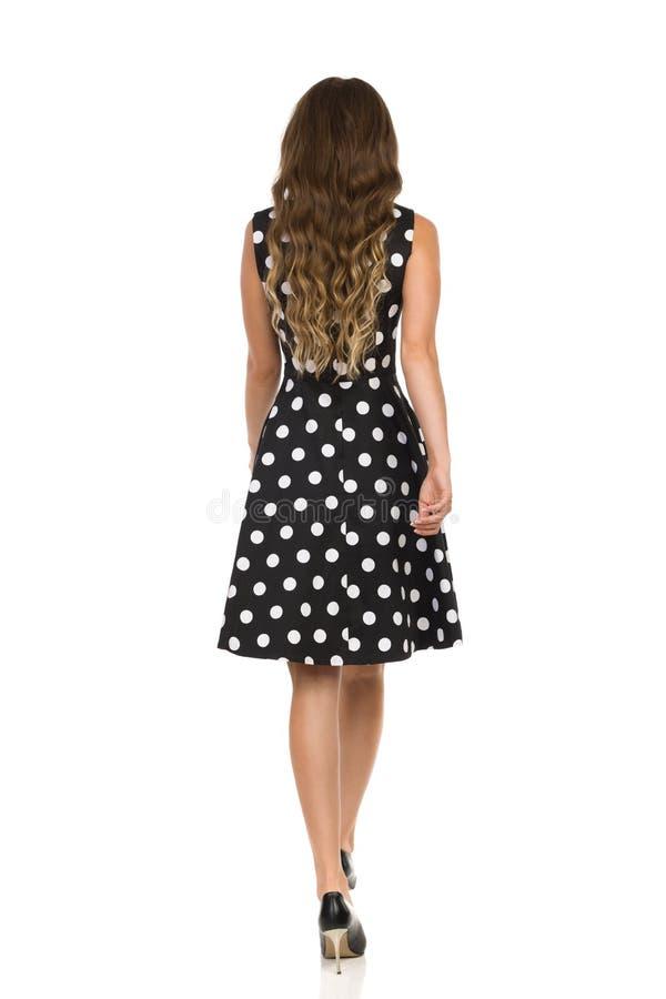 Οπισθοσκόπος της περπατώντας όμορφης νέας γυναίκας στο μαύρο διαστιγμένο φόρεμα κοκτέιλ και τα υψηλά τακούνια στοκ εικόνα