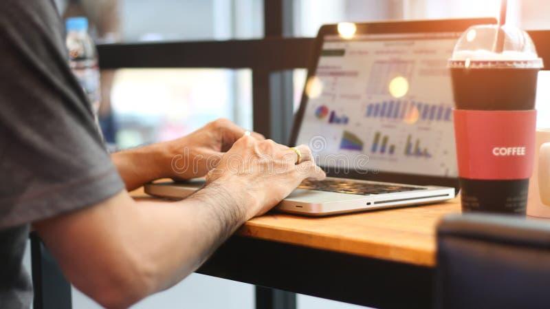 Οπισθοσκόπος του αρσενικού που εργάζεται στο lap-top του σε μια καφετερία στοκ φωτογραφίες