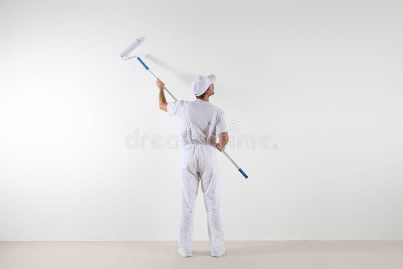 Οπισθοσκόπος του ατόμου ζωγράφων που εξετάζει τον κενό τοίχο, με το χρώμα rolle στοκ εικόνες
