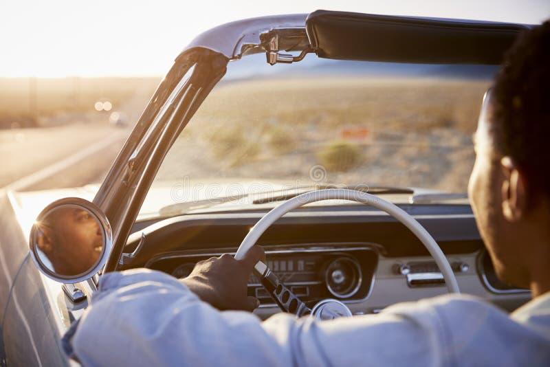Οπισθοσκόπος του ατόμου στο οδικό ταξίδι που το κλασικό μετατρέψιμο αυτοκίνητο προς το ηλιοβασίλεμα στοκ εικόνα