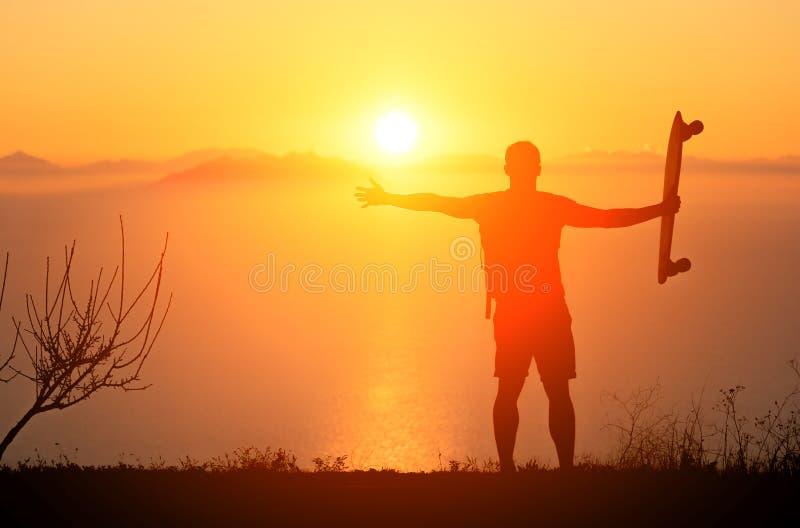 Οπισθοσκόπος του ατόμου hipster με το longboard και του σακιδίου πλάτης το καλοκαίρι στην παραλία σε μια τροπική θέση Εναλλακτικέ στοκ φωτογραφία