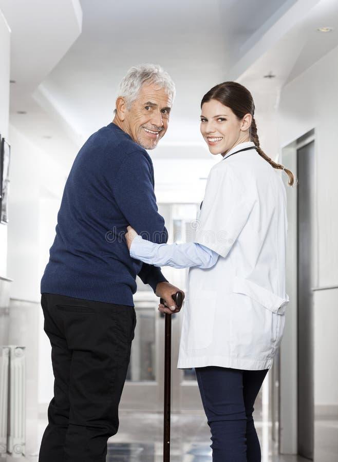 Οπισθοσκόπος του ευτυχούς περπατήματος γιατρών με τον ανώτερο ασθενή στοκ εικόνα