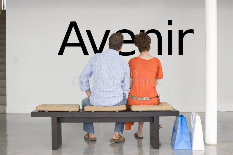 Οπισθοσκόπος του ζεύγους που κάθεται στον πάγκο που διαβάζει το γαλλικό κείμενο Avenir (μέλλον) στον τοίχο στοκ εικόνες