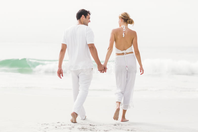 Οπισθοσκόπος του ζεύγους που περπατά στην παραλία στοκ εικόνες