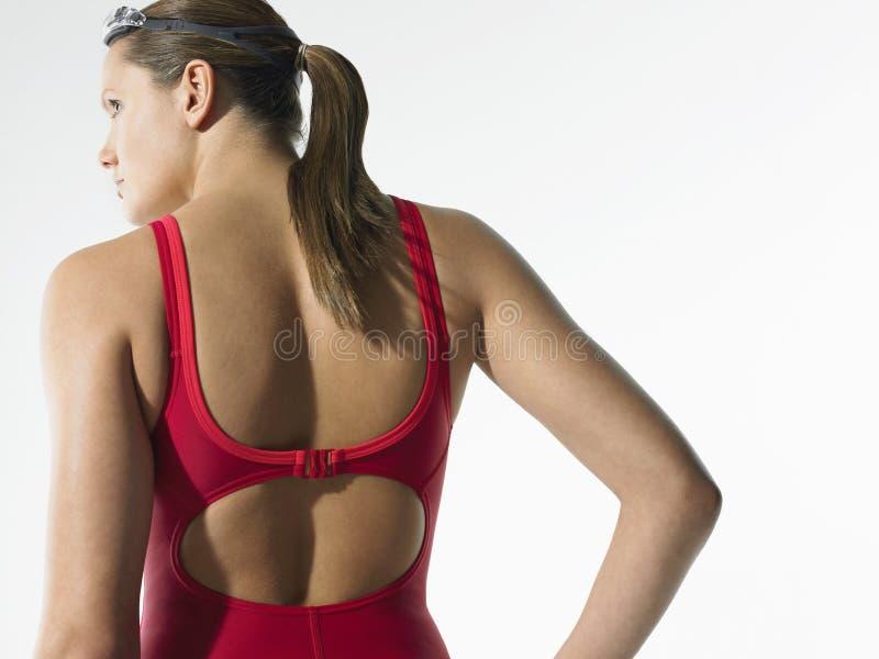 Οπισθοσκόπος του θηλυκού κολυμβητή σε κόκκινο Swimwear στοκ εικόνα