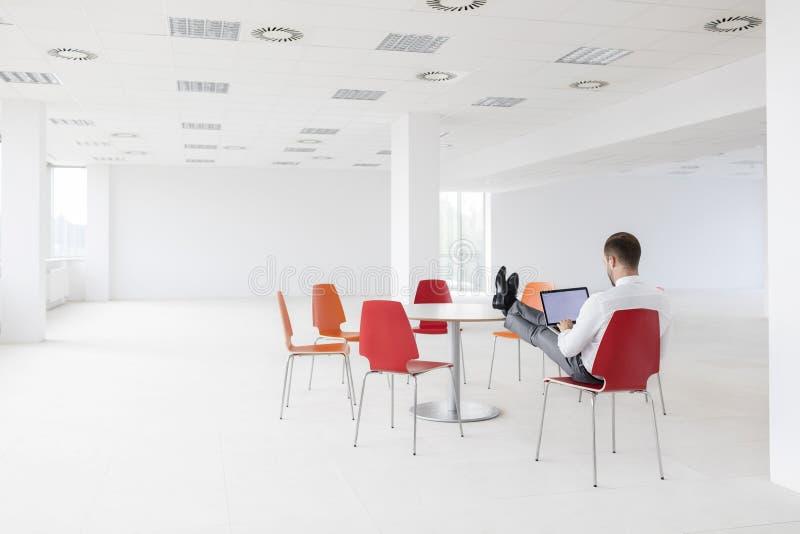 Οπισθοσκόπος του νέου επιχειρηματία που χρησιμοποιεί το lap-top στο νέο γραφείο στοκ φωτογραφίες με δικαίωμα ελεύθερης χρήσης