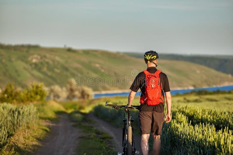 Οπισθοσκόπος του νέου οδηγώντας ποδηλάτου ποδηλατών στο δρόμο του τομέα στοκ εικόνες