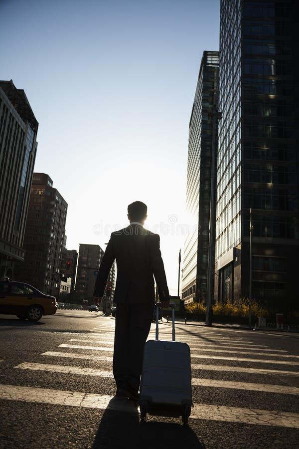 Οπισθοσκόπος του νέου περπατήματος επιχειρηματιών κάτω από την οδό με τις αποσκευές στοκ εικόνα