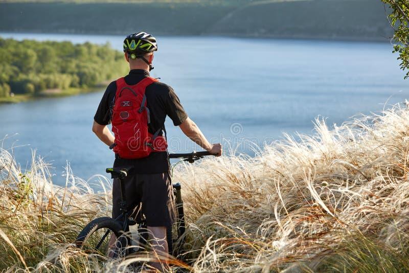 Οπισθοσκόπος του νέου ποδηλάτη που στέκεται με το ποδήλατο βουνών ενάντια στον όμορφο ποταμό στοκ εικόνες
