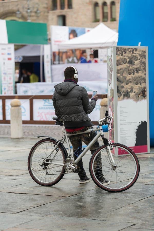 Οπισθοσκόπος του νεαρού άνδρα με τα ακουστικά που κάθονται στο ποδήλατο και που χρησιμοποιούν Smartphone στην οδό πόλεων: Άνθρωπο στοκ εικόνα