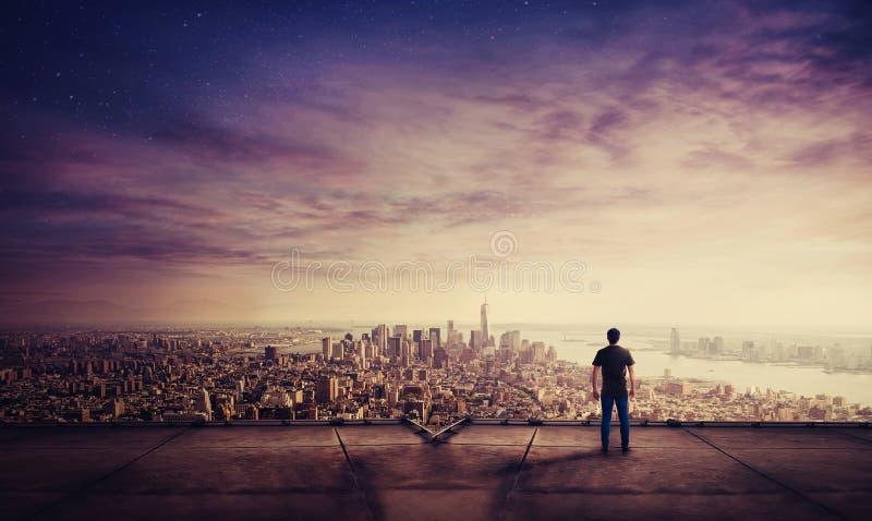 Οπισθοσκόπος του νεαρού άνδρα που στέκεται στη στέγη ενός ηλιοβασιλέματος προσοχής ουρανοξυστών πέρα από το μεγάλο ορίζοντα πόλεω στοκ φωτογραφίες