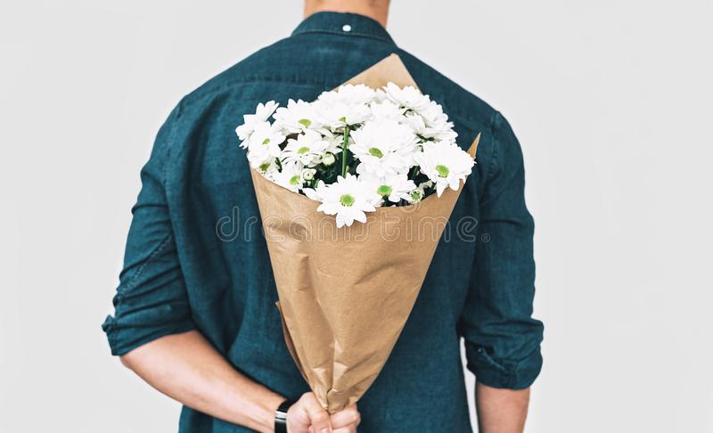 Οπισθοσκόπος του νεαρού άνδρα που χαμογελά και που παραδίδει μια ανθοδέσμη των άσπρων λουλουδιών Ελκυστικό αρσενικό πρότυπο με μι στοκ φωτογραφία με δικαίωμα ελεύθερης χρήσης