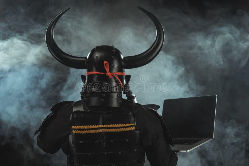 οπισθοσκόπος του Σαμουράι στο παραδοσιακό τεθωρακισμένο με το lap-top στο σκοτεινό υπόβαθρο στοκ εικόνα
