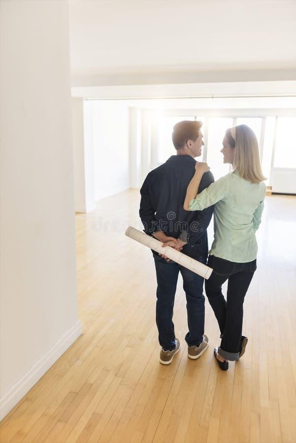 Οπισθοσκόπος του ώριμου ζεύγους που στέκεται στο καινούργιο σπίτι στοκ φωτογραφία με δικαίωμα ελεύθερης χρήσης