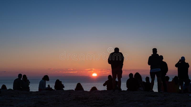 Οπισθοσκόπος των ανθρώπων που προσέχουν το ηλιοβασίλεμα στοκ εικόνες
