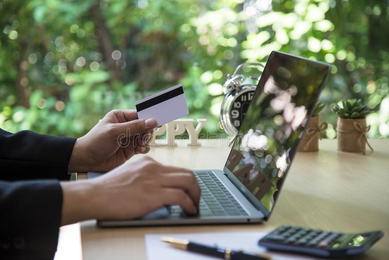 Οπισθοσκόπος των σύγχρονων χεριών επιχειρηματιών που κρατούν τους αριθμούς δακτυλογράφησης πιστωτικών καρτών στο πληκτρολόγιο υπο στοκ εικόνα με δικαίωμα ελεύθερης χρήσης