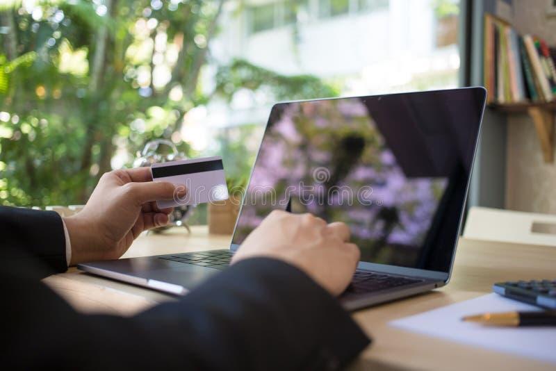 Οπισθοσκόπος των σύγχρονων χεριών επιχειρηματιών που κρατούν τους αριθμούς δακτυλογράφησης πιστωτικών καρτών στο πληκτρολόγιο υπο στοκ φωτογραφίες