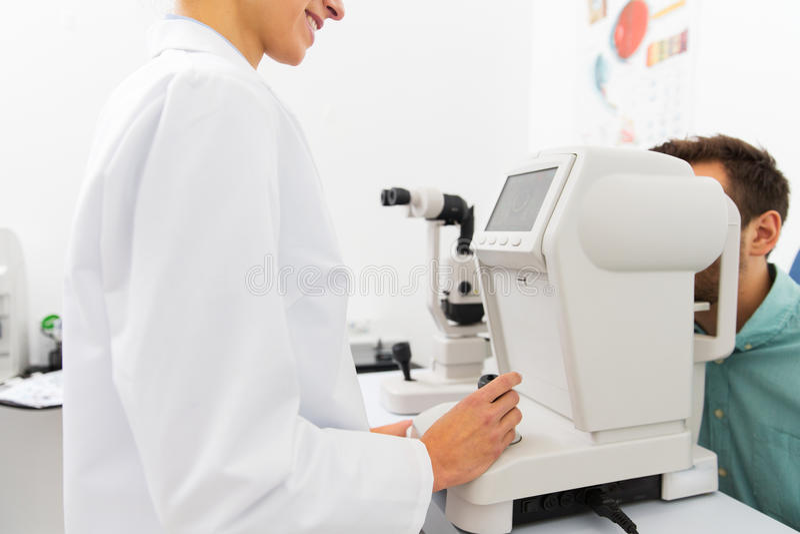 Οπτικός με το autorefractor και ασθενής στην κλινική στοκ εικόνα