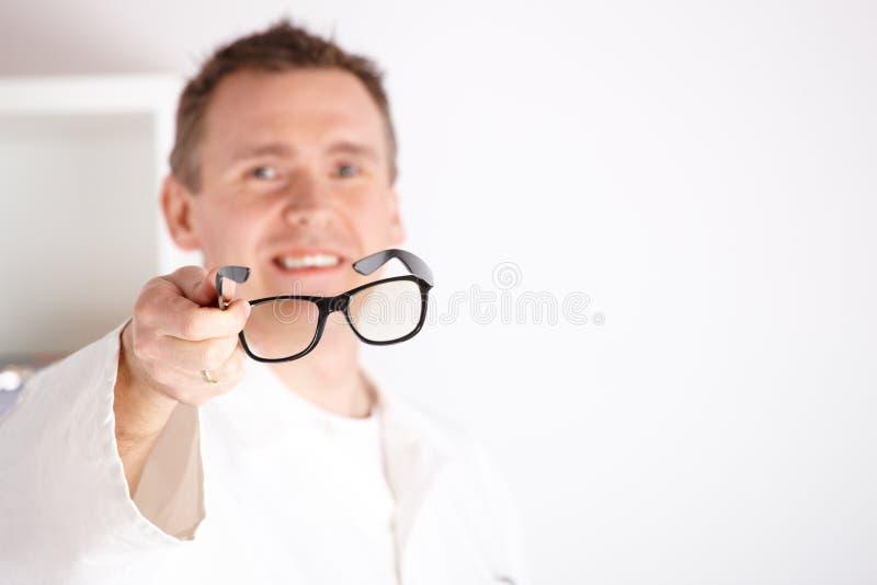 Οπτικός που προσφέρει τα γυαλιά στοκ εικόνα με δικαίωμα ελεύθερης χρήσης