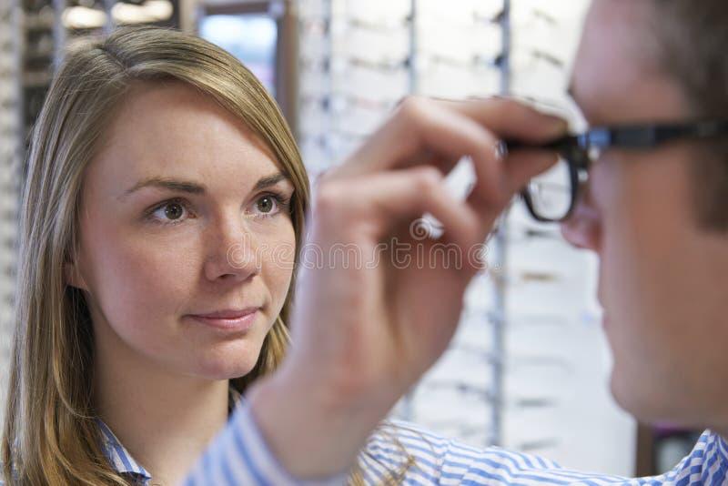 Οπτικός που συμβουλεύει τον πελάτη για την επιλογή των γυαλιών στοκ φωτογραφία με δικαίωμα ελεύθερης χρήσης