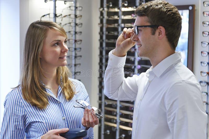 Οπτικός που συμβουλεύει τον πελάτη για την επιλογή των γυαλιών στοκ εικόνες