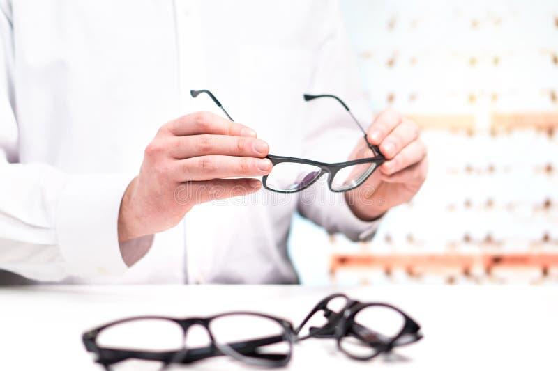 Οπτικός στα γυαλιά εκμετάλλευσης καταστημάτων Γιατρός ματιών με τους φακούς στοκ εικόνες
