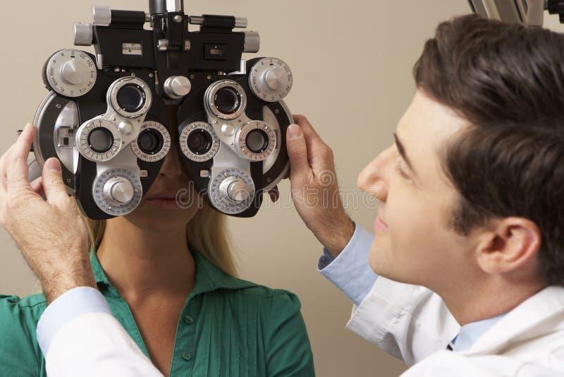 Οπτικός στη χειρουργική επέμβαση που δίνει τη δοκιμή ματιών γυναικών στοκ φωτογραφία με δικαίωμα ελεύθερης χρήσης