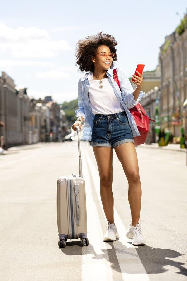Οπτιμιστής θηλυκός τουρίστας που ψάχνει τη θέση ξενοδοχείων στοκ φωτογραφία με δικαίωμα ελεύθερης χρήσης