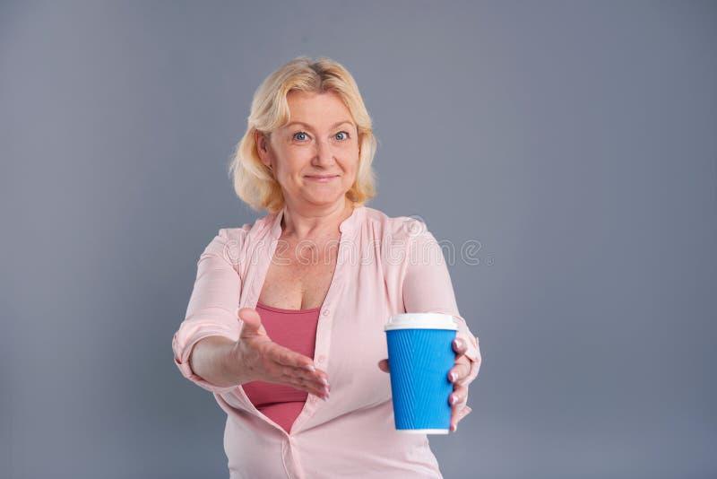 Οπτιμιστής μέσης ηλικίας γυναίκα που δείχνει στο φλυτζάνι καφέ στοκ φωτογραφία με δικαίωμα ελεύθερης χρήσης