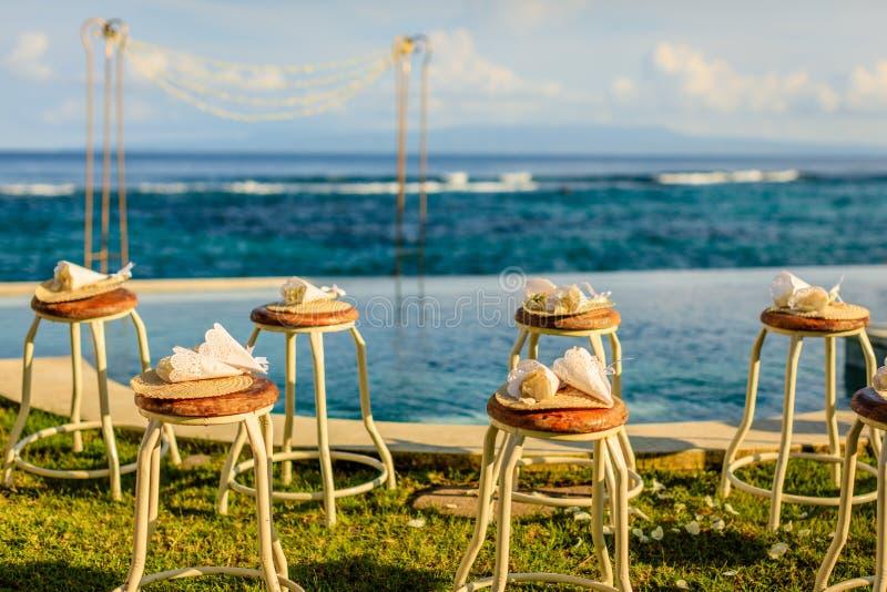 Οργάνωση γαμήλιας τελετής κοντά στον ωκεανό στο ηλιοβασίλεμα - οι καρέκλες για τους φιλοξενουμένους με τα πέταλα λουλουδιών και τ στοκ εικόνες