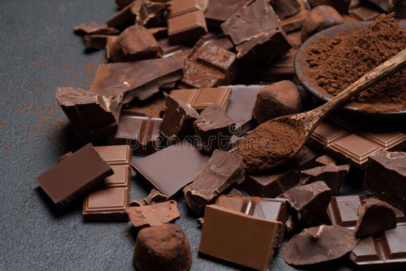 Οργανικά κομμάτια σοκολάτας σκοταδιού ή γάλακτος, σκόνη κακάου και κα στοκ φωτογραφίες