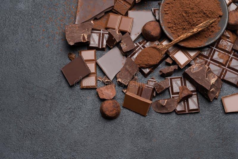 Οργανικά κομμάτια σοκολάτας σκοταδιού ή γάλακτος, σκόνη κακάου και κα στοκ εικόνες
