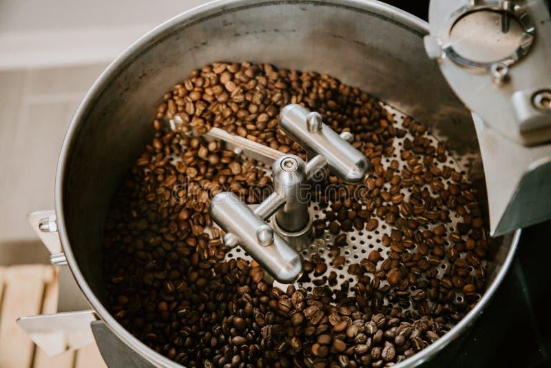 Οργανικά φασόλια καφέ που ψήνουν βιομηχανικό Roaster φασολιών καφέ και που δροσίζουν στο μηχανικό τηγάνι ανακατώματος στοκ εικόνες