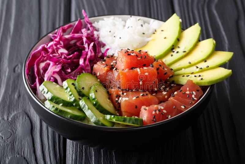 Οργανική τροφή: κύπελλο σπρωξίματος τόνου με το ρύζι, φρέσκα αγγούρια, κόκκινο αμάξι στοκ εικόνες