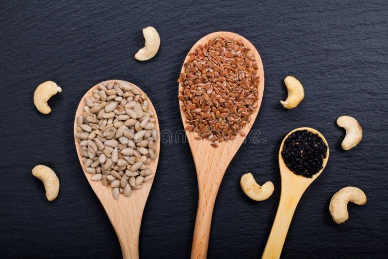 Οργανικοί σπόροι ηλίανθων, σπόροι λιναριού και σουσάμι στο ξύλινο κουτάλι και το ακατέργαστο υπόβαθρο πετρών πλακών καρυδιών των  στοκ εικόνες