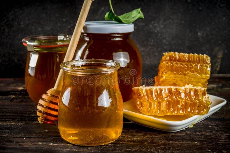 Οργανικό αγροτικό μέλι στα βάζα με τις κηρήθρες στοκ εικόνα
