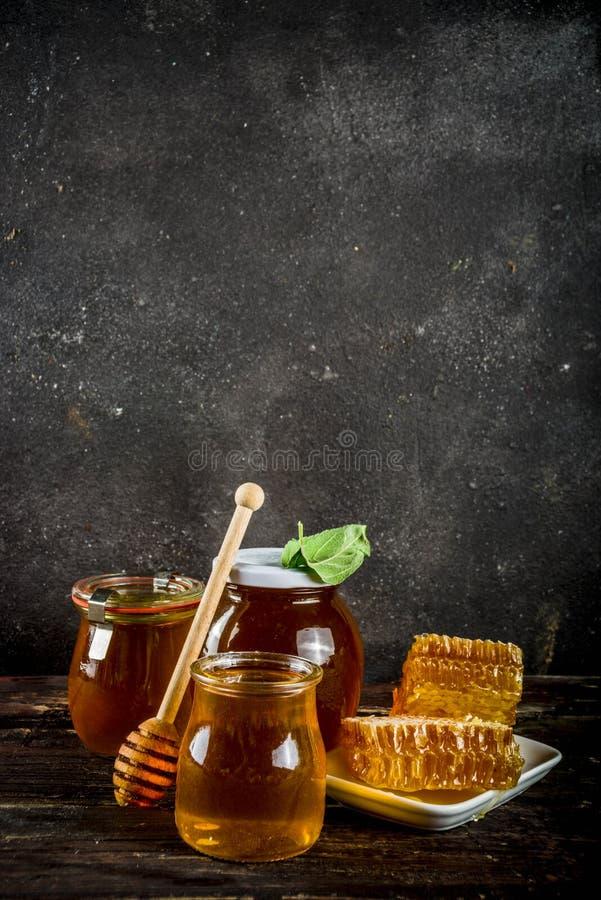 Οργανικό αγροτικό μέλι στα βάζα με τις κηρήθρες στοκ εικόνα με δικαίωμα ελεύθερης χρήσης