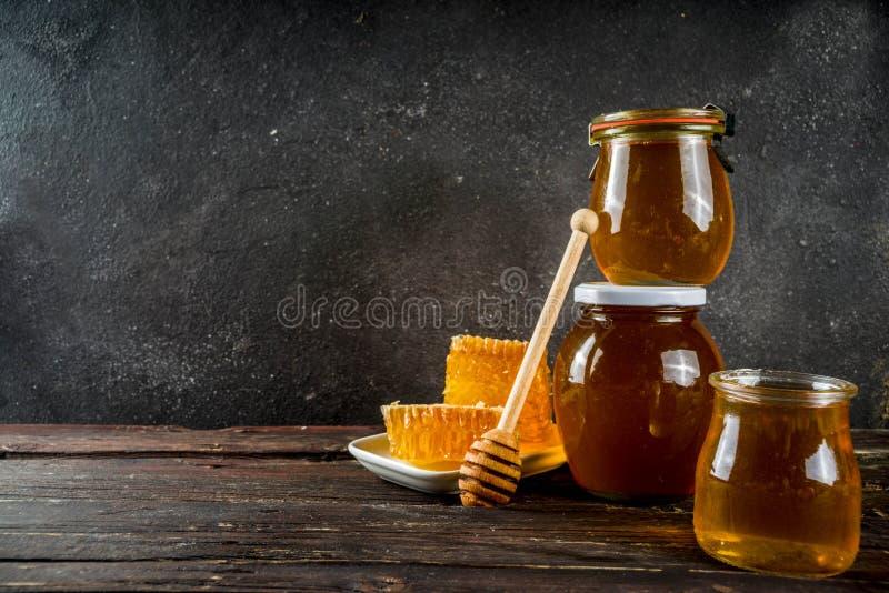 Οργανικό αγροτικό μέλι στα βάζα με τις κηρήθρες στοκ εικόνες