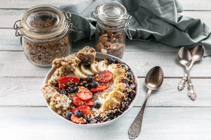 Οργανικό κύπελλο προγευμάτων προγευμάτων υγιές: Τυρί εξοχικών σπιτιών, granola, μπανάνες, φράουλες, βακκίνια και ξεφγμένο ρύζι Ξύ στοκ φωτογραφίες