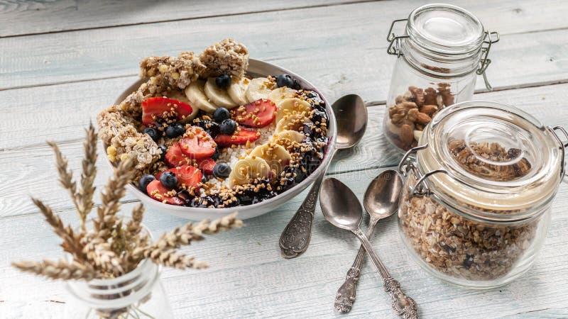 Οργανικό κύπελλο προγευμάτων προγευμάτων υγιές: Τυρί εξοχικών σπιτιών, granola, μπανάνες, φράουλες, βακκίνια και ξεφγμένο ρύζι Ξύ στοκ φωτογραφία