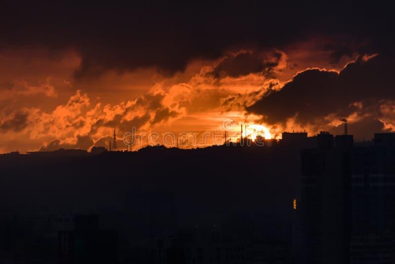 Οργιμένος ηλιοβασίλεμα ενάντια στα εργοστάσια στο ridgeline στοκ εικόνα