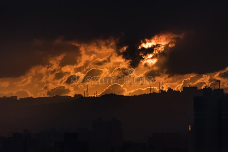 Οργιμένος ηλιοβασίλεμα ενάντια στα εργοστάσια στο ridgeline στοκ εικόνες