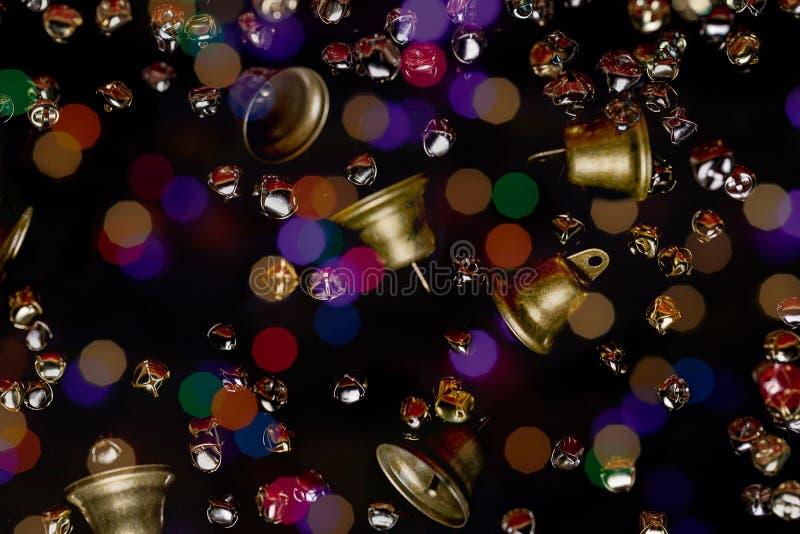 Ορείχαλκο, χρώμιο και χρυσοκίτρινο Jingle Bells και παραδοσιακές καμπάνες που επικαλύπτονται μπροστά από ένα μαύρο φόντο καλυμμέν στοκ φωτογραφία με δικαίωμα ελεύθερης χρήσης